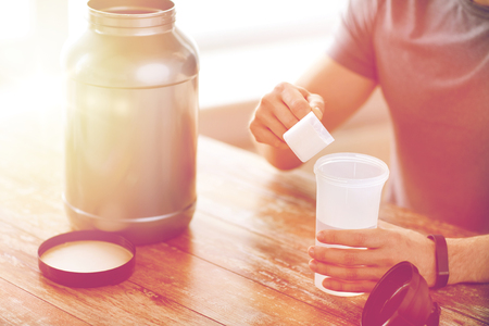 casein: sport, fitness, healthy lifestyle and people concept - close up of man in fitness bracelet with jar and bottle preparing protein shake