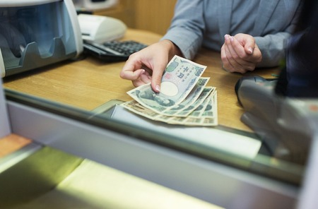 exchanger: people, withdrawal, saving and finance concept - clerk counting cash money at bank office or currency exchanger Stock Photo