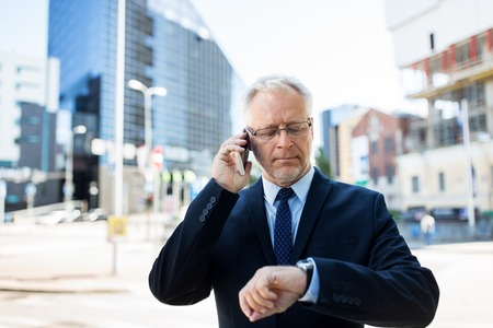 punctuality: business, technology, time, punctuality and people concept - senior businessman calling on smartphone an looking at wristwatch or smart watch on his hand in city Stock Photo