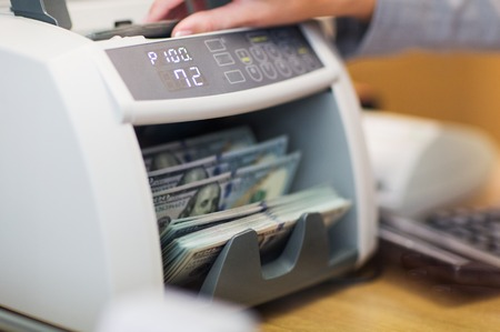 people, finance and cash concept - clerk hand counting dollars with electronic money counter machine at bank office or currency exchanger Stok Fotoğraf