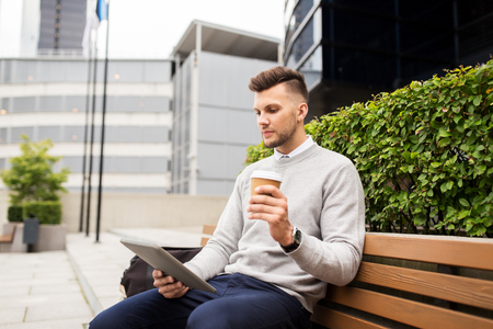 metrosexual: business, education, technology, communication and people concept - creative man with tablet pc computer drinking coffee from paper cup and sitting on city street bench