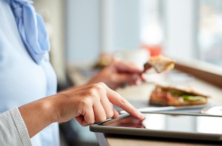 fast food restaurant: food, dinner, technology and people concept - woman with tablet pc computer eating salmon panini sandwich at restaurant Stock Photo