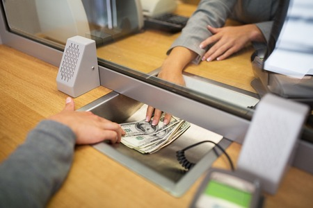 people, withdrawal, saving and finance concept - clerk giving cash money to customer at bank office or currency exchanger