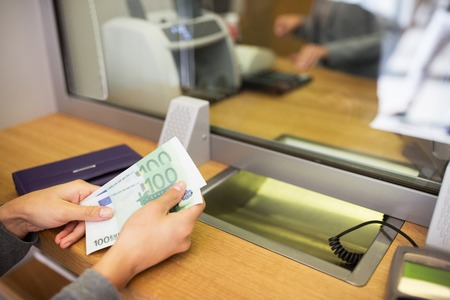 dinero euros: las personas, la retirada, el ahorro y la financiación de concepto - las manos con dinero en efectivo en la oficina bancaria o cambiador de divisas Foto de archivo