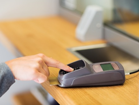 pin code: finance, money, technology, payment and people concept - close up of hand entering pin code to card reader terminal