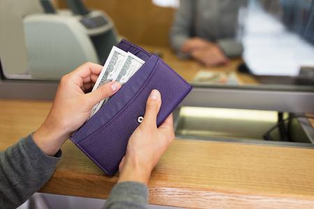 mensen, sparen en financià «n concept - handen met contant geld en portemonnee op bankkantoor of valuta wisselaar