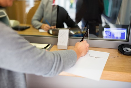 teller: people and finance concept - customer with pen and paper writing application at bank office