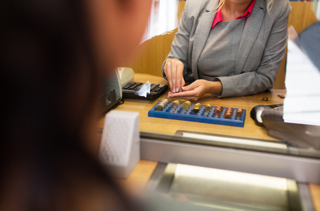 exchanger: people, money, saving and finance concept - clerk counting coins for customer at bank office or currency exchanger Stock Photo