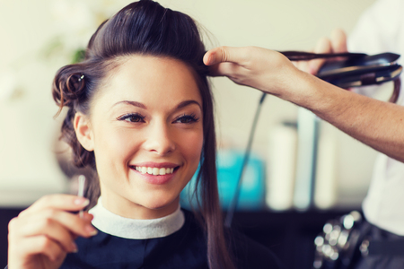 happy woman with stylist making hairdo at salon Imagens
