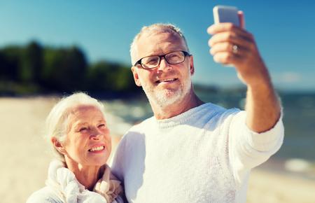 couple outdoor: happy senior couple hugging on summer beach