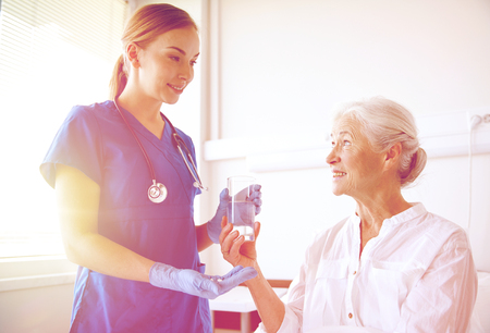 doctor giving glass: nurse giving medicine to senior woman at hospital Stock Photo