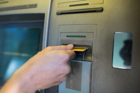 automatic transaction machine: close up of hand inserting card to atm machine