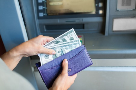 emoney: close up of hand withdrawing money at atm machine