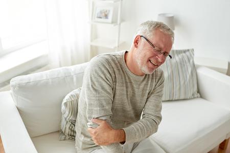 senior men: unhappy senior man suffering elbow pain at home Stock Photo