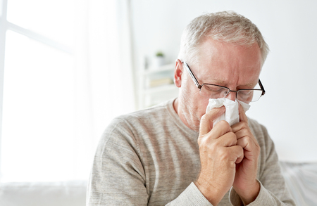 zieke hogere man met papieren doekjes zijn neus blaast Stockfoto