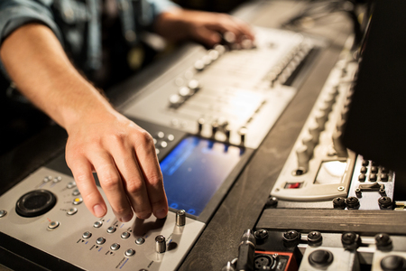 adjuster: man using mixing console in music recording studio