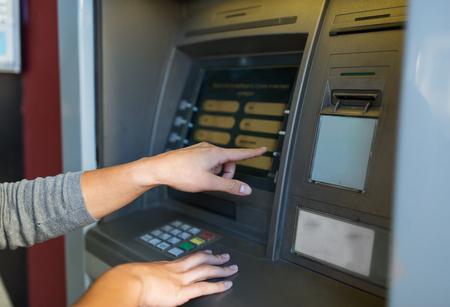 emoney: close up of hands choosing option on atm machine
