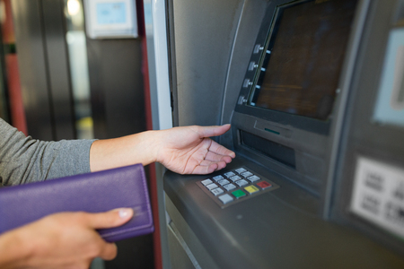 automatic transaction machine: close up of hands withdrawing cash at atm machine Foto de archivo