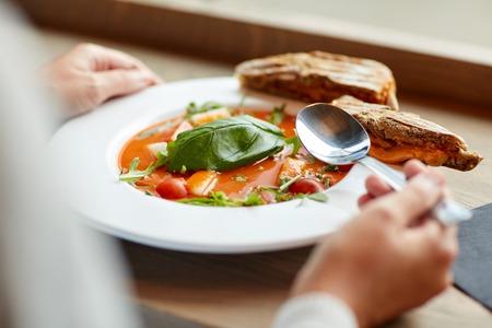 woman eating gazpacho soup at restaurant
