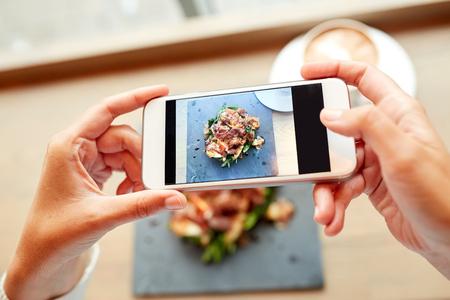Las manos con alimentos teléfono inteligente fotografiar Foto de archivo - 68455010