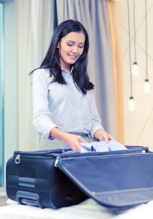 'young things': businesswoman packing things in suitcase