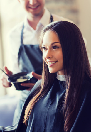 happy young woman coloring hair at salon Stock Photo