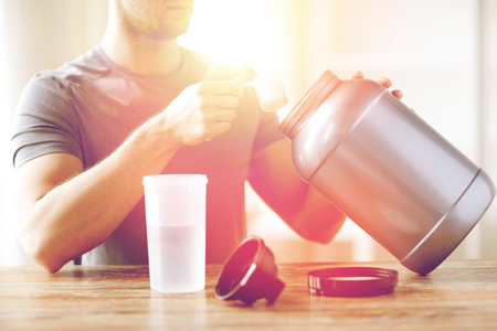 casein: close up of man with protein shake bottle and jar Stock Photo