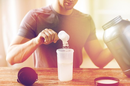 close up of man with protein shake bottle and jar Stockfoto