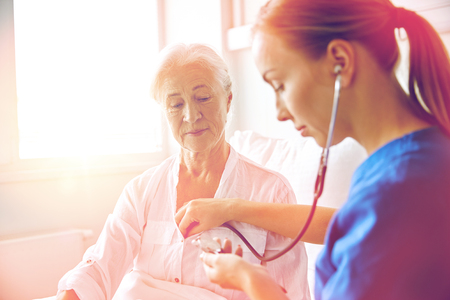 nurse with stethoscope and senior woman at clinic Imagens