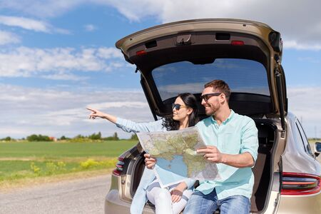 hatchback: happy man and woman with road map at hatchback car