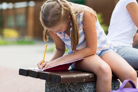 school yard: student girl writing to notebook at school yard