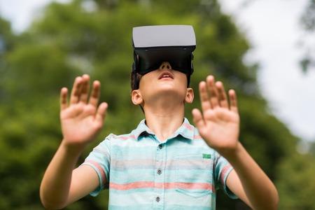 niños felices: muchacho con el casco de realidad virtual al aire libre