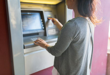 emoney: close up of woman inserting card to atm machine Stock Photo