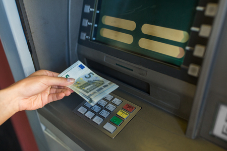 withdrawing: close up of hand withdrawing money at atm machine