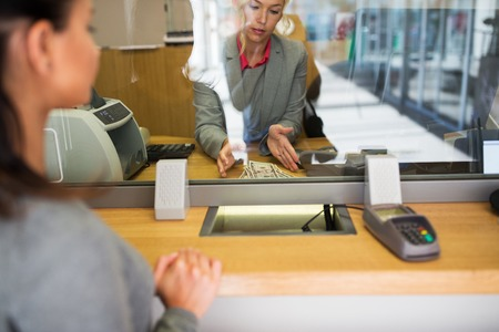 clerk with cash money and customer at bank office Stockfoto