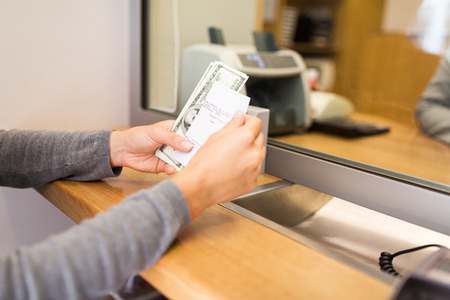 withdrawing: customer with money and receipt at bank counter