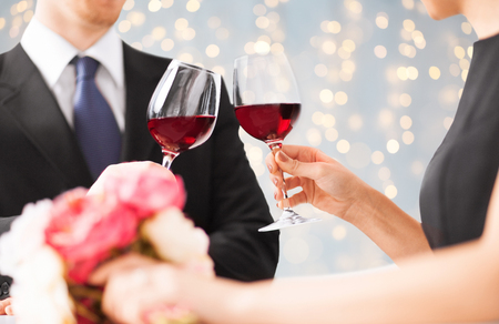 close up of couple clinking red wine glasses photo