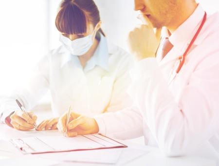 doctor and nurse writing prescription paper photo