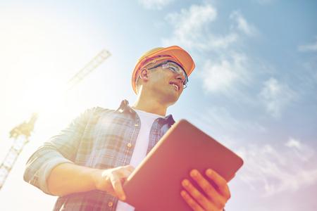 constructeur en hardhat avec tablette pc à la construction Banque d'images