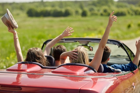 happy friends driving in cabriolet car at country Foto de archivo