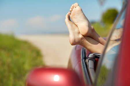 beautiful feet: feet of young woman in convertible car at summer Stock Photo