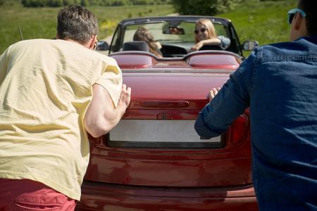 empujando: amigos felices empujando el coche roto cabriolet