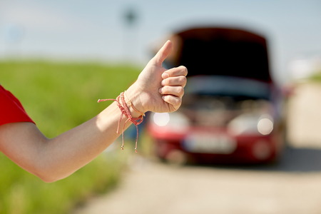 woman with broken car hitching at countryside