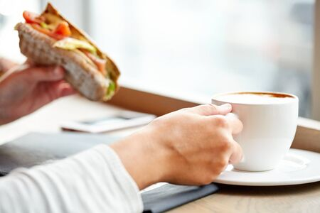 panino: woman drinking coffee and eating sandwich at cafe