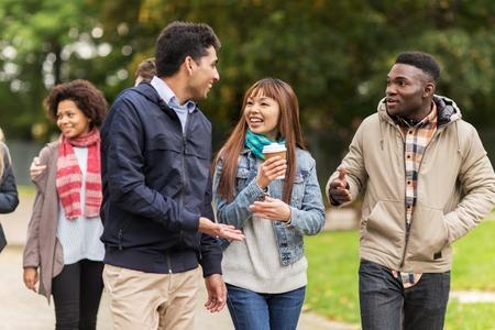 gelukkige vrienden wandelen langs de herfst park Stockfoto