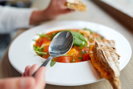 gaspacho: woman eating gazpacho soup at restaurant