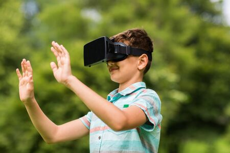 niños jugando videojuegos: muchacho con el casco de realidad virtual al aire libre