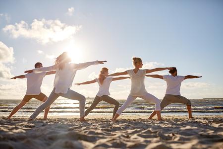 Gruppe von Menschen, die Yoga-Übungen am Strand machen Standard-Bild