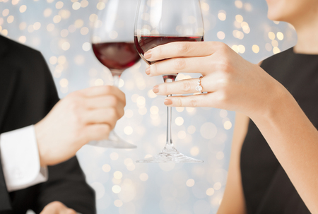 close up of engaged couple with wine glasses photo
