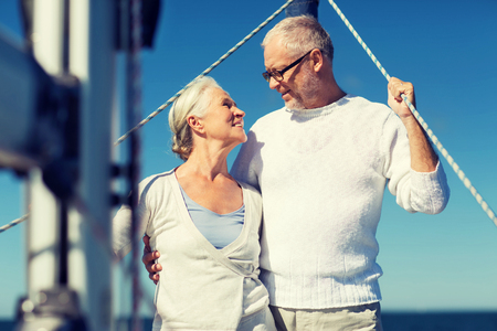 senior couple hugging on sail boat or yacht in sea